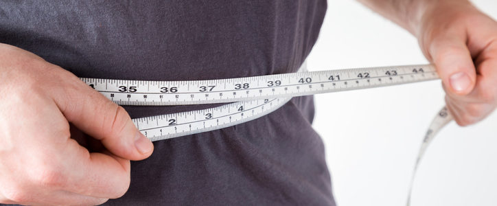 man measuring waistline